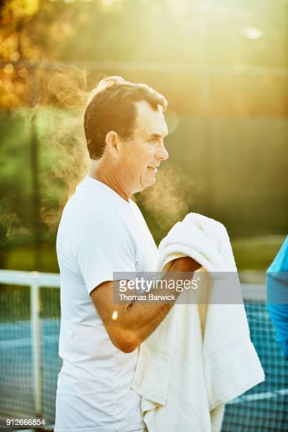 Mature male tennis player using towel after early morning workout