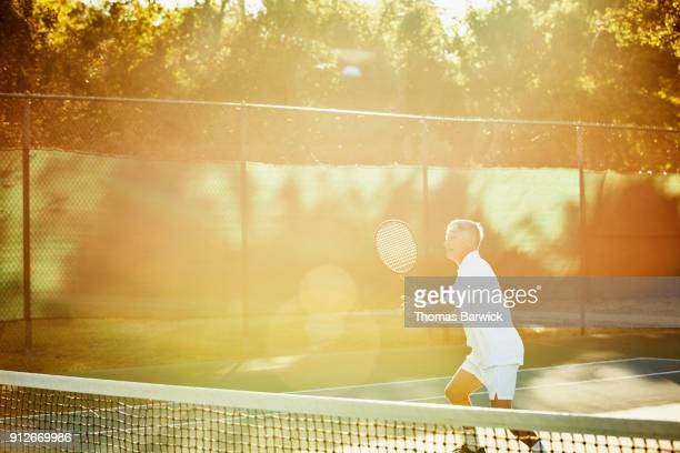 Mature male tennis player waiting to hit return at net during early morning tennis match