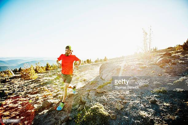Mature male trail running across mountainside