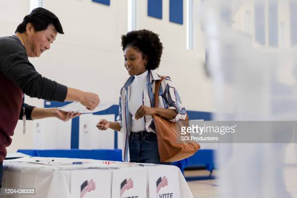 mature male volunteer explains voting document to young woman - local politics stock pictures, royalty-free photos & images