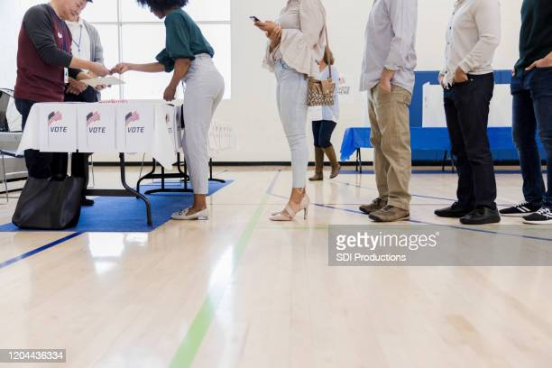 mature male volunteers help unrecognizable people lined up to vote - polling station stock pictures, royalty-free photos & images
