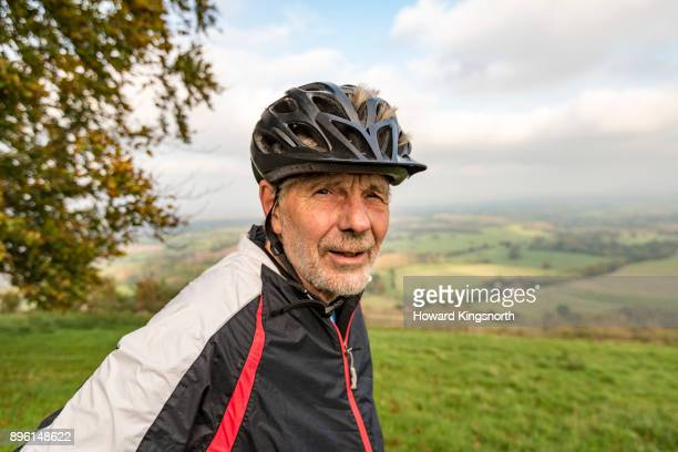 mature male with cycling helmet in green landscape