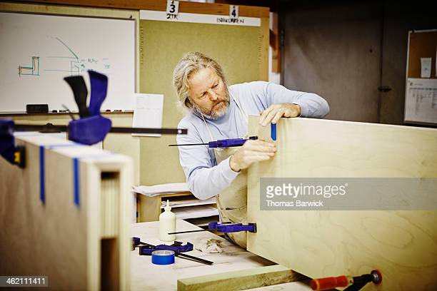 Mature male woodworker in shop building cabinets
