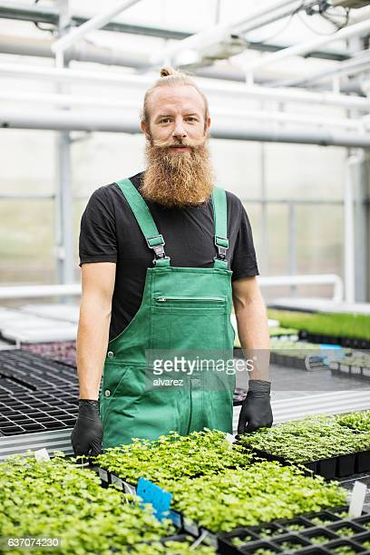 Mature male worker standing in greenhouse