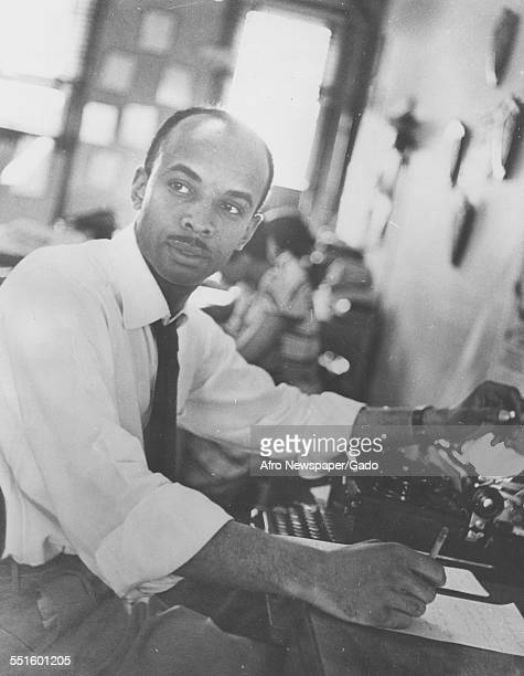 A mature man a reporter seated at a typewriter in the offices of a newspaper the old Afro American office building holding a pen making notes...