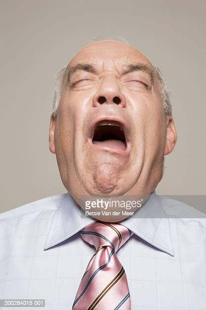 Mature man about to sneeze, eyes closed, close-up