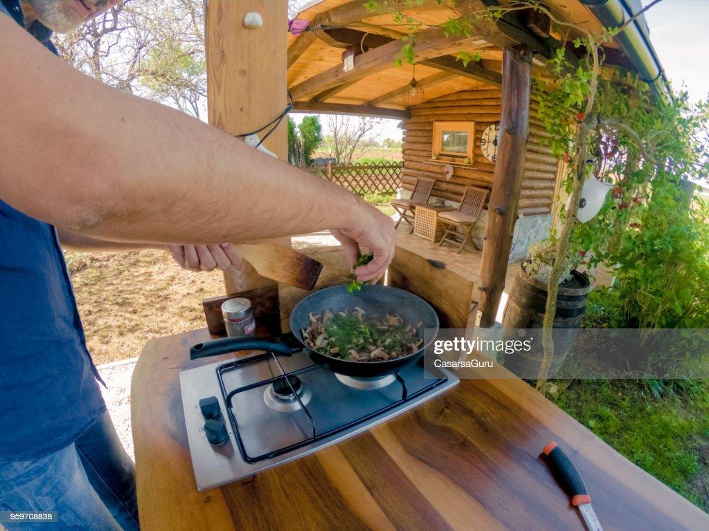 Reifen Sie Mann Braten Pilze Petersilie hinzufügen : Stock-Foto
