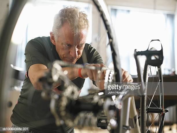 mature man adjusting bicycle chain - adjusting stock pictures, royalty-free photos & images