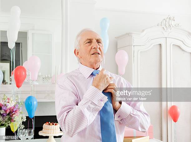 mature man adjusting his tie. - adjusting necktie stock pictures, royalty-free photos & images