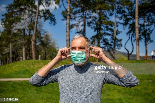 mature man adjusting protective mask outdoors in public park - strap stock pictures, royalty-free photos & images