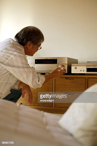 A mature man adjusting stereo