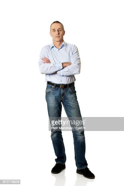 mature man against white background - spijkerbroek stockfoto's en -beelden