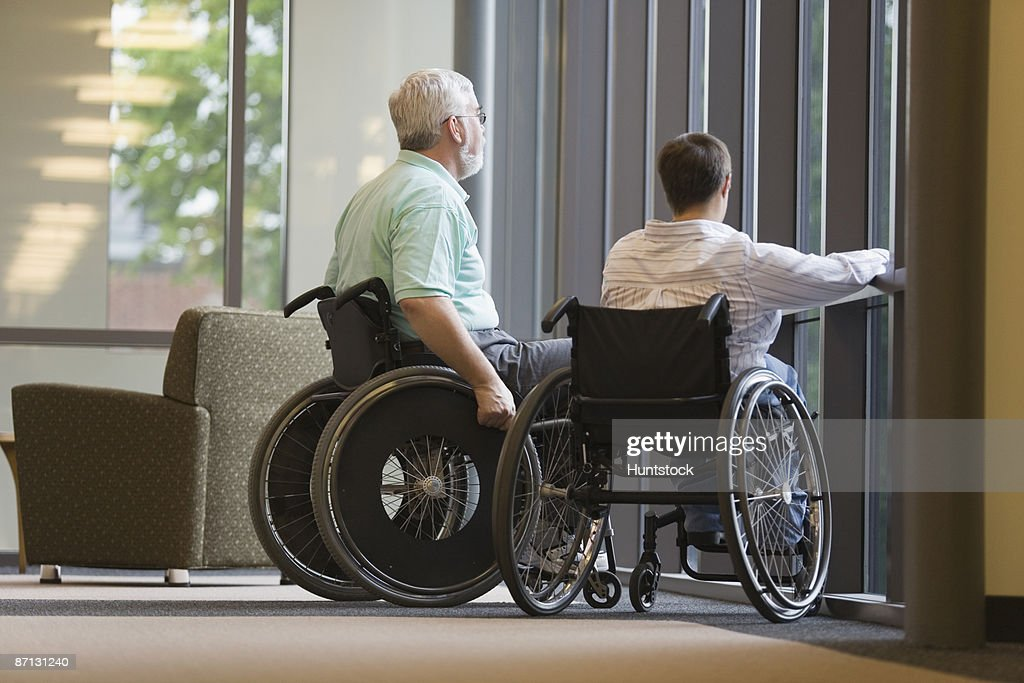Mature man and a young woman sitting in wheelchairs in a library : Photo