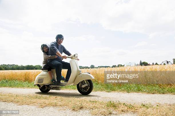 Mature man and daughter riding motor scooter along dirt track