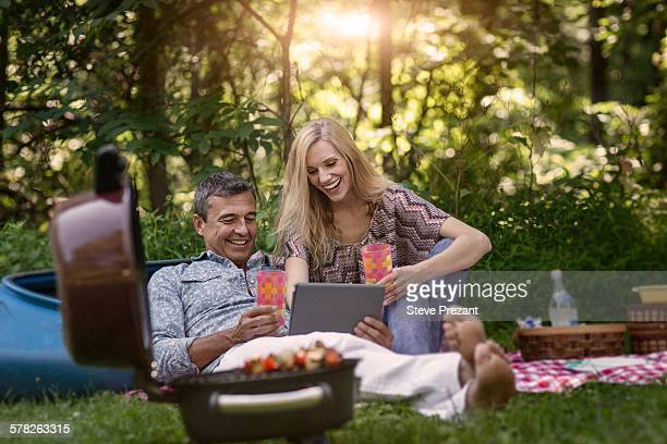 Mature man and girlfriend looking at digital tablet whilst having picnic barbecue