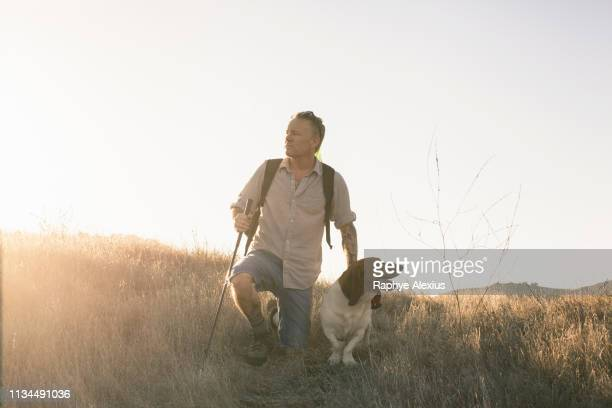 mature man and his basset hound taking a break from hiking in santa monica mountains, california, usa - one man only stock pictures, royalty-free photos & images