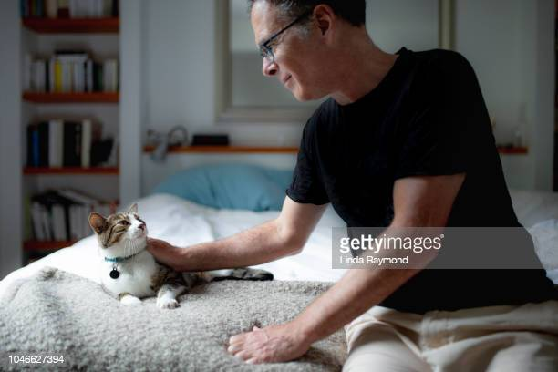 a mature man and his cat - domestic animals stock pictures, royalty-free photos & images