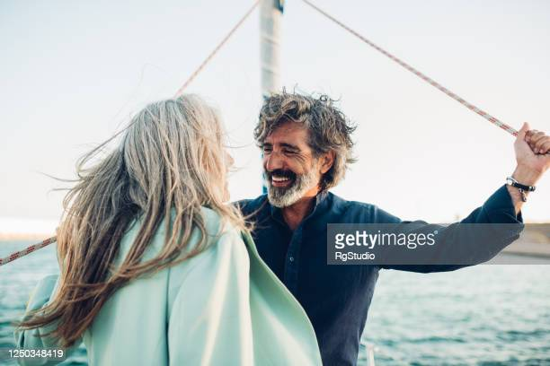 mature man and his wife enjoying sailing with their yacht - wealth stock pictures, royalty-free photos & images