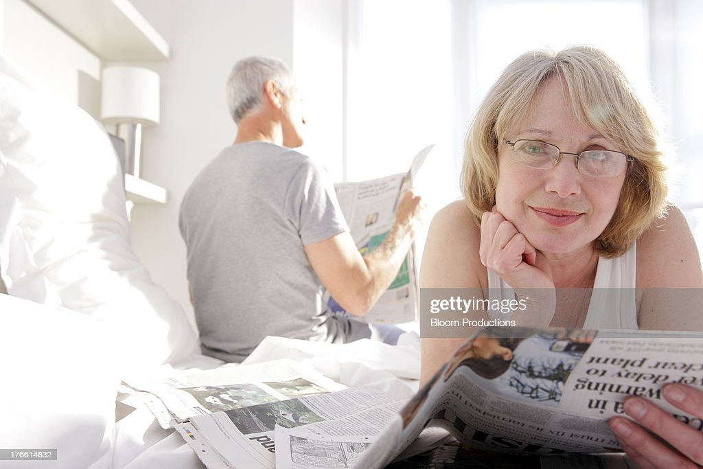 Mature man and lady reading newspapershe papers : Stock Photo