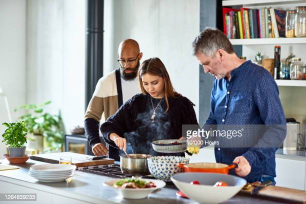 mature man and mid adult couple serving food at home - doing a favor stock pictures, royalty-free photos & images