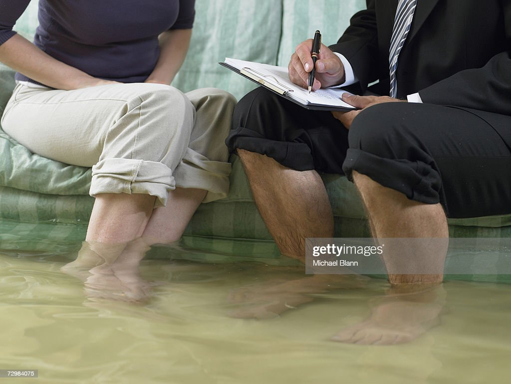 Mature man and mid adult woman sitting on sofa with water over their ankles, low section : Stock Photo