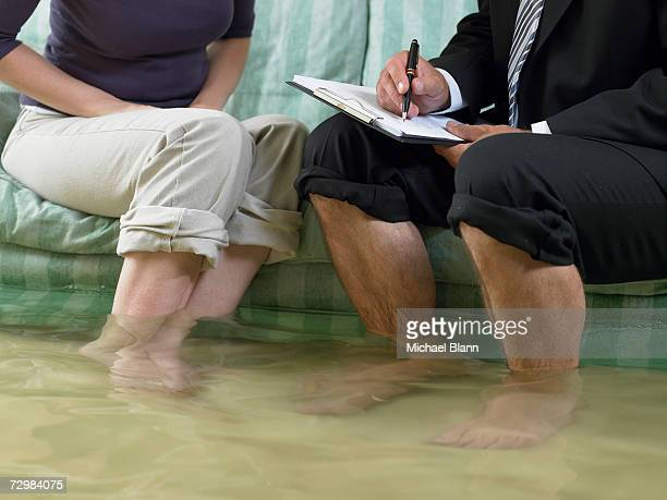 mature man and mid adult woman sitting on sofa with water over their ankles, low section - flooding stock photos and pictures