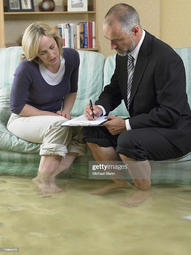 Mature man and mid adult woman sitting on sofa with water over their ankles : Stock Photo