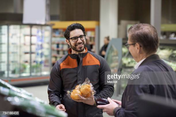 Mature man and sales clerk talking while holding vegetables at supermarket