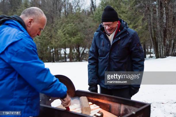 """mature man and senior father making a fire outdoors in winter - """"martine doucet"""" or martinedoucet stock pictures, royalty-free photos & images"""