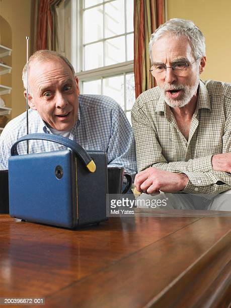 Mature man and senior man sitting on sofa listening to radio