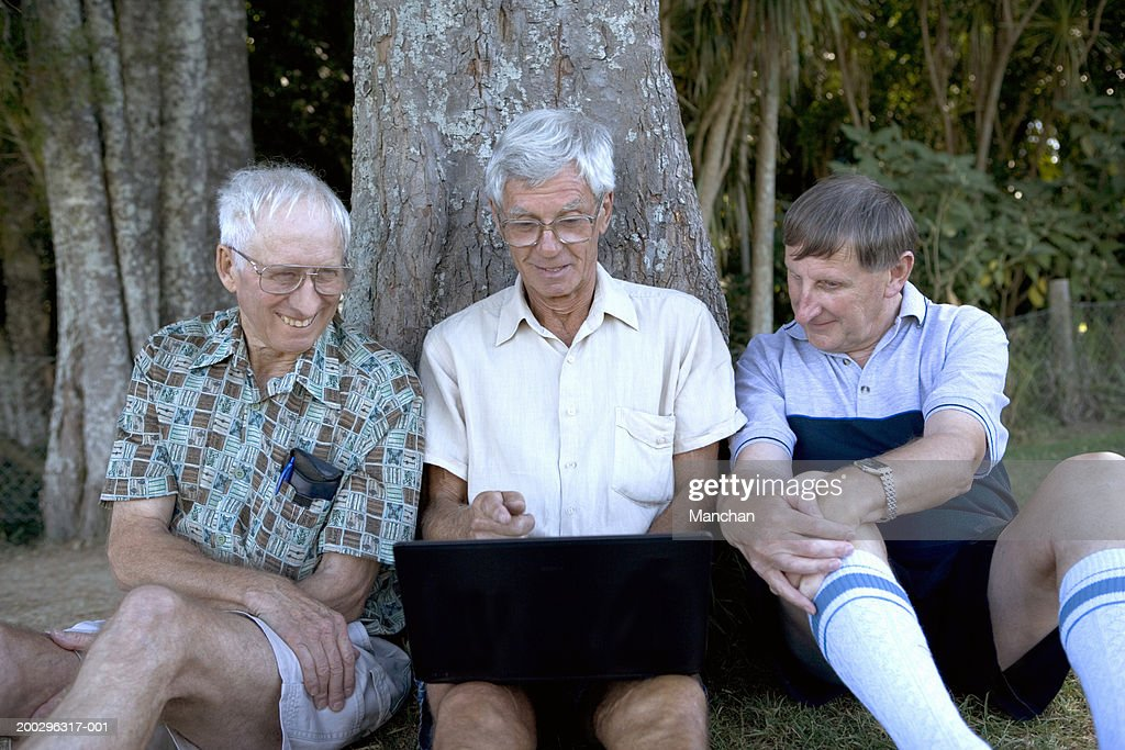 Mature man and senior men by tree, looking at laptop screen, smiling : Stock Photo