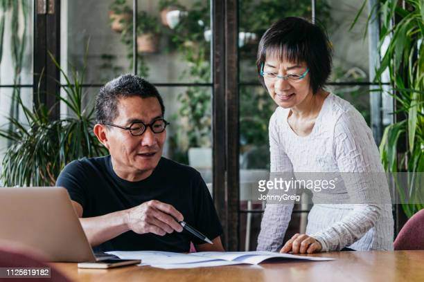 mature man and senior woman looking at home finances with laptop - business finance and industry stock pictures, royalty-free photos & images