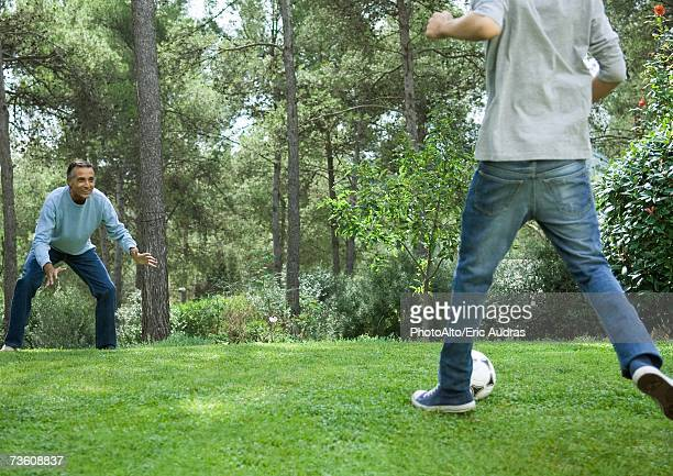 mature man and teenage boy playing soccer - chutar - fotografias e filmes do acervo