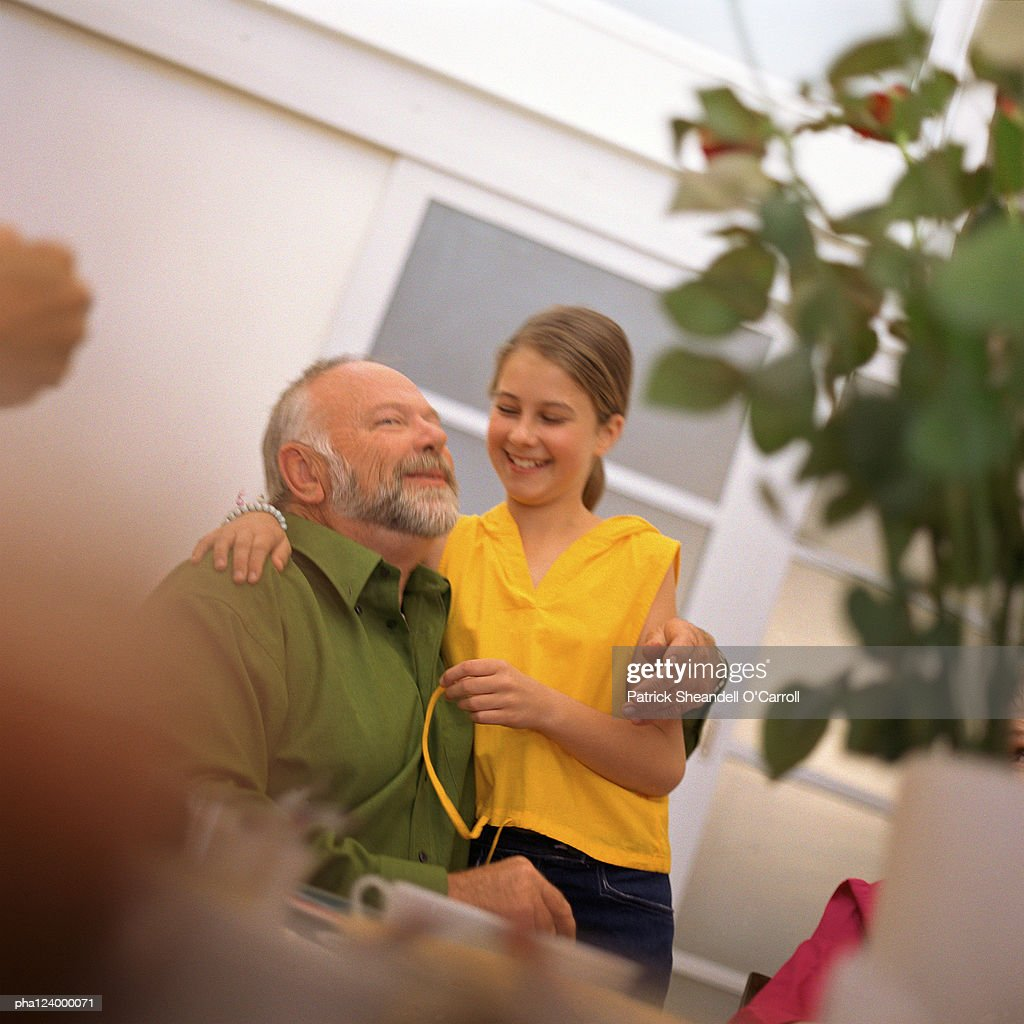 Mature man and teenage girl arm in arm, smiling : Stockfoto