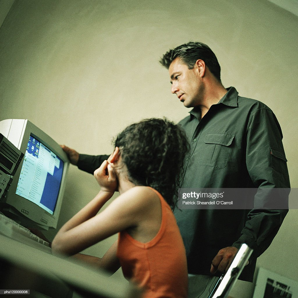 Mature man and teenage girl in front of computer : Stockfoto