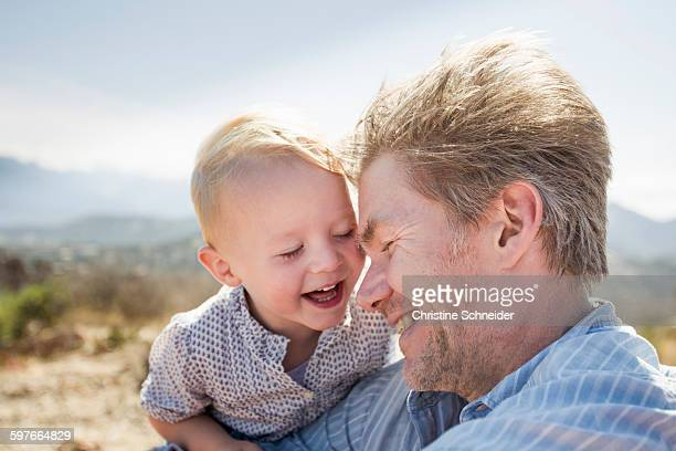 mature man and toddler daughter laughing, calvi, corsica, france - leanintogether stock pictures, royalty-free photos & images
