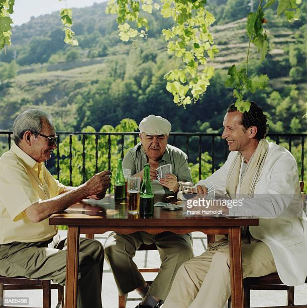 Mature man and two elderly men playing cards outdoors