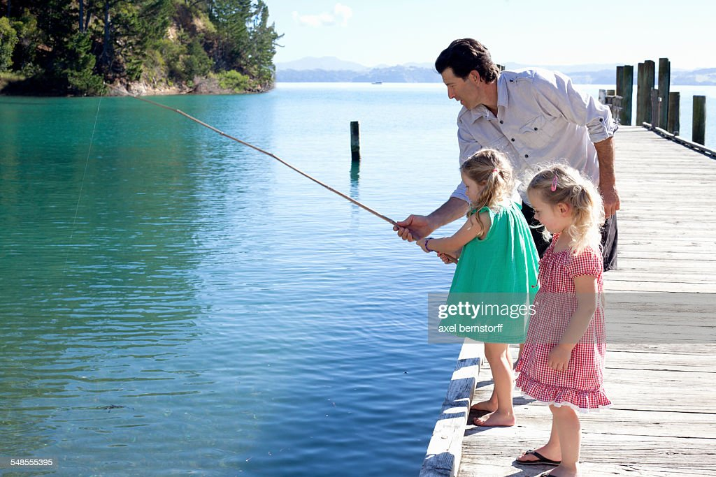 Mature man and two young girls fishing from pier, New Zealand : Stock Photo