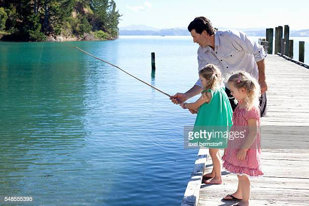 Mature man and two young girls fishing from pier, New Zealand