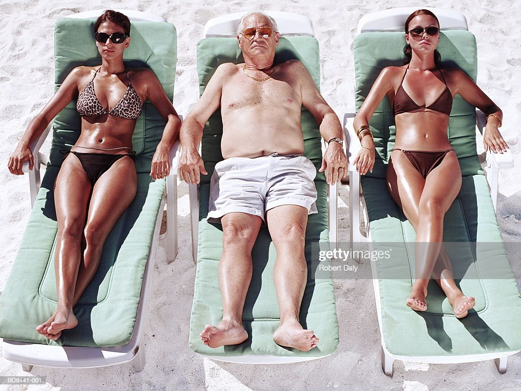 mature man and two young women on sun loungers on beach stock photo