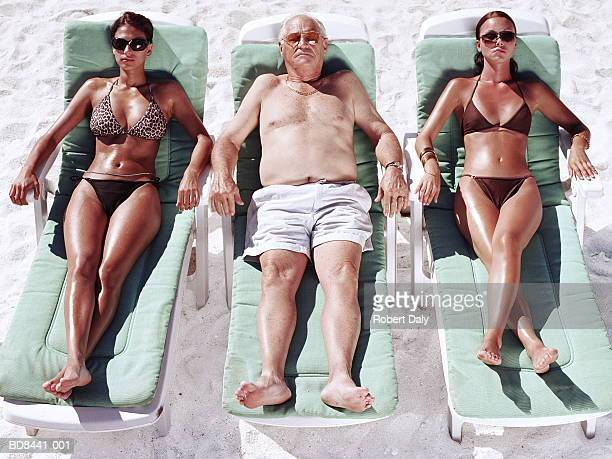mature man and two young women on sun loungers on beach - man met een groep vrouwen stockfoto's en -beelden