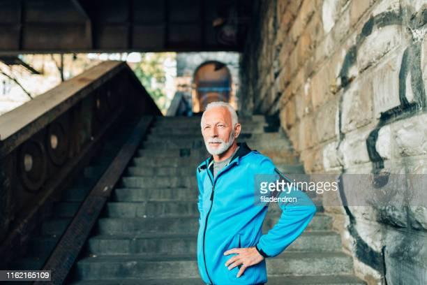 hombre maduro y entrenamiento urbano - sporting term fotografías e imágenes de stock