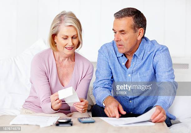 Mature man and wife calculating expenses using calculator