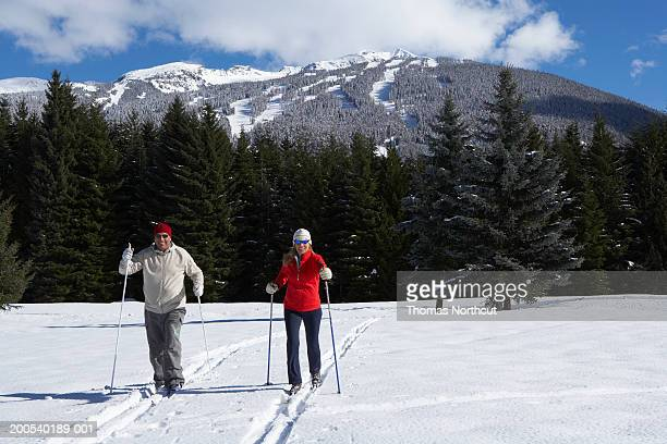 Mature man and woman cross-country skiing