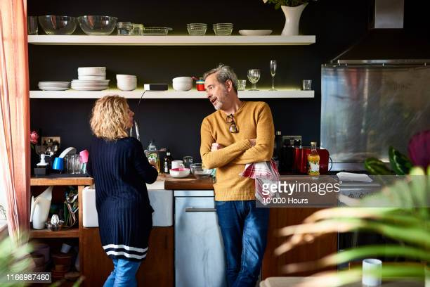 mature man and woman doing dishes together in kitchen - couples showering stock pictures, royalty-free photos & images