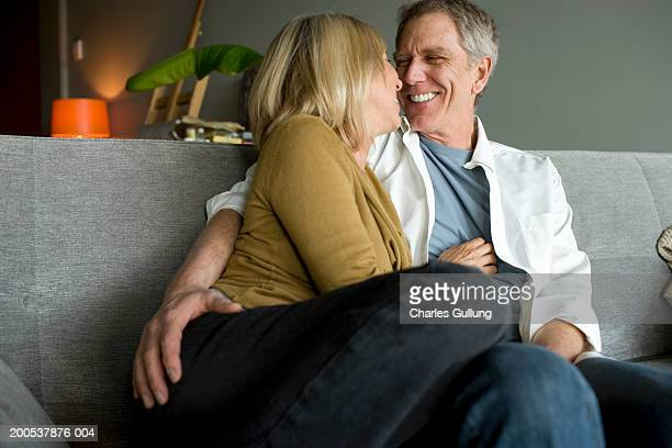 Mature man and woman embracing and laughing on sofa