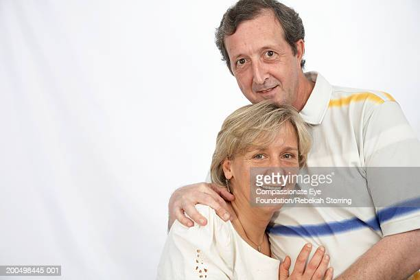 Mature man and woman embracing and smiling, portrait