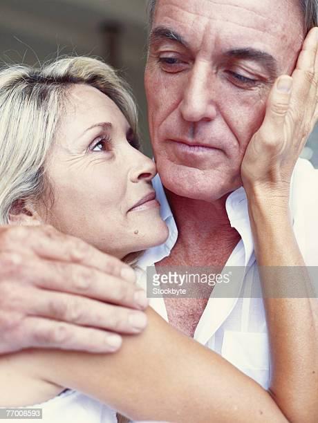 Mature man and woman embracing, close-up