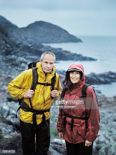 Mature man and woman hiking on nature trail in rain