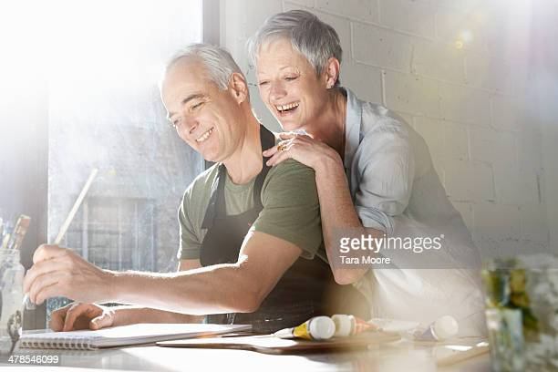 mature man and woman in artist studio - 50 59 years stock pictures, royalty-free photos & images